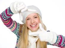 La ragazza sorridente nell'inverno copre l'inquadratura con le mani Fotografie Stock
