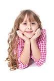 La ragazza sorridente riccia si trova su un pavimento fotografia stock