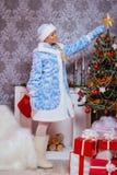 La ragazza sorridente si agghinda l'albero di Natale immagini stock