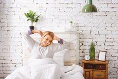 La ragazza sorridente si sveglia in camera da letto Immagine Stock
