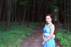 La ragazza sorridente sta su un sentiero per pedoni della foresta scura Fotografia Stock Libera da Diritti