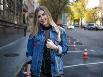 La ragazza sorridente sveglia con capelli lussuosi in un rivestimento del denim sta nel parcheggio per le automobili all'aperto immagini stock libere da diritti