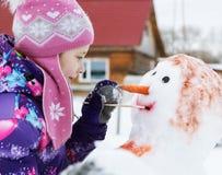 La ragazza sorridente sveglia dipinge un pupazzo di neve Fotografia Stock
