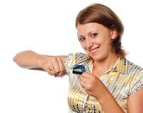 La ragazza sorridente taglia una carta di credito Fotografia Stock