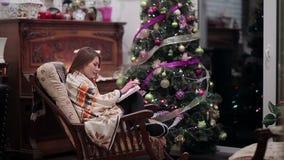 La ragazza sotto il plaid ha letto il libro vicino all'albero di Natale stock footage