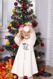 La ragazza sotto l'abete giudica un fiocco di neve disponibile Fotografia Stock