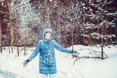 La ragazza sparge la neve sotto forma di un cuore fotografia stock