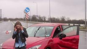 La ragazza spaventata che parla sul telefono dopo un incidente stradale nella pioggia, automobile ? rotta stock footage