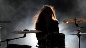 La ragazza specialmente formata gioca i tamburi Fondo nero del fumo Siluetta archivi video