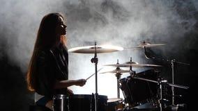 La ragazza specialmente formata gioca i tamburi Fondo nero del fumo Siluetta video d archivio
