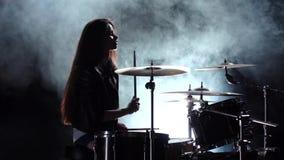 La ragazza specialmente formata gioca i tamburi Fondo nero del fumo Siluetta Movimento lento stock footage