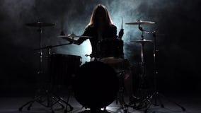 La ragazza specialmente formata gioca i tamburi Fondo nero del fumo Siluetta Movimento lento archivi video