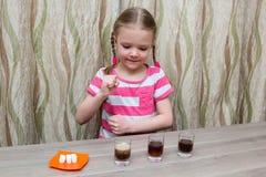 La ragazza spende l'esperienza chimica alla tavola a casa Fotografie Stock