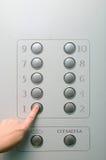 La ragazza spinge un bottone nell'elevatore Immagine Stock