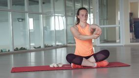 La ragazza sportiva affascinante fa l'esercizio d'allungamento difficile sulla stuoia della palestra mentre si prepara nella pale Fotografia Stock