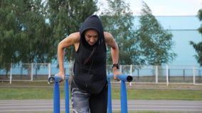 La ragazza sportiva che fa il tricipite si esercita sui fasci video d archivio