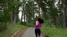 La ragazza sportiva passa il parco di mattina Movimento lento stock footage