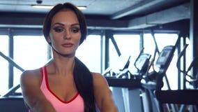 La ragazza sportiva sta facendo gli esercizi con le teste di legno pesanti video d archivio