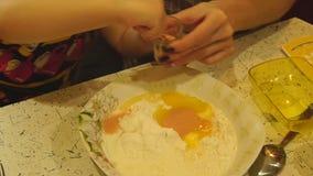 La ragazza spruzza il lievito secco per impastare la pasta stock footage