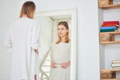 La ragazza sta ad uno specchio ed è dietro lo stomaco Immagine Stock Libera da Diritti