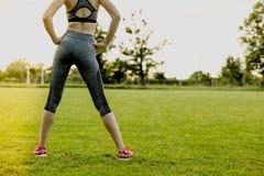 La ragazza sta allungando prima di correre, preparante il concetto Fotografie Stock Libere da Diritti