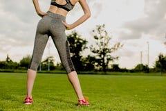 La ragazza sta allungando prima di correre, preparante il concetto Immagini Stock