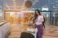 La ragazza sta aspettando un amico Viaggiando all'aeroporto fotografie stock
