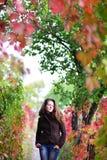 La ragazza sta in autunno con gli occhi chiusi Immagine Stock
