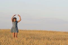 La ragazza sta ballando nel campo dell'avena Immagini Stock Libere da Diritti