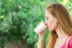 La ragazza sta bevendo il caffè asportabile nel parco Fotografie Stock Libere da Diritti