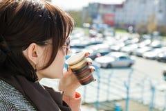 La ragazza sta bevendo il caffè su un fondo confuso del bokeh Immagini Stock Libere da Diritti
