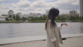 La ragazza sta camminando lungo il fiume archivi video
