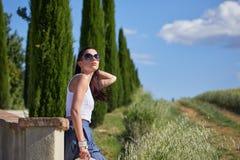 La ragazza sta camminando lungo la strada fra i campi Fotografie Stock