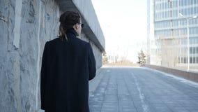 La ragazza sta camminando lungo la parete video d archivio
