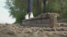 La ragazza sta camminando su un blocco di pietra sulla sponda del fiume stock footage