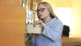 La ragazza sta cercando la documentazione necessaria negli archivi delle biblioteche archivi video