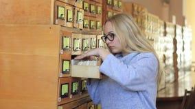 La ragazza sta cercando la documentazione necessaria negli archivi delle biblioteche video d archivio