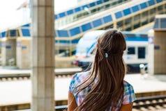 La ragazza sta con lei indietro alla stazione ed esamina il treno di partenza Immagini Stock