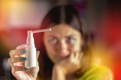 La ragazza sta considerando uno spruzzo per il naso Trattamento dei freddo, influenza Immagine Stock Libera da Diritti