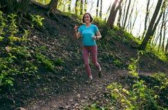 La ragazza sta correndo nel legno fotografia stock libera da diritti