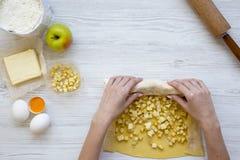 La ragazza sta cucinando la torta di mele o lo strudel su fondo di legno bianco Vista superiore Da sopra fotografia stock libera da diritti