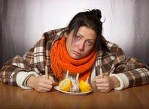 La ragazza sta curanda per l'aglio ed il limone di malattia Fotografia Stock