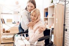 La ragazza sta curando la donna anziana a casa La ragazza è portare presente per la donna fotografia stock libera da diritti