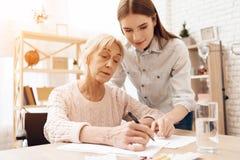 La ragazza sta curando la donna anziana a casa La ragazza sta aiutando la donna scrive fotografia stock libera da diritti