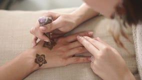 La ragazza sta dipingendo i fiori sulle mani della donna dell'amico che usando il hennè, mehendi d'avanguardia video d archivio