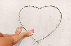 La ragazza sta disegnando il cuore sulla sabbia immagine stock