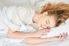 La ragazza sta dormendo sul letto bianco Fotografie Stock
