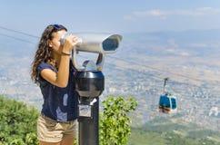 La ragazza sta esaminando binoculare a gettoni Fotografie Stock Libere da Diritti
