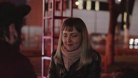 La ragazza sta esaminando il ragazzo Si siedono in un caffè nella sera stock footage