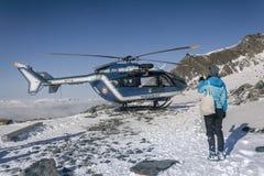 La ragazza sta esaminando l'elicottero nelle alpi francesi, sopra le nuvole Immagine Stock Libera da Diritti